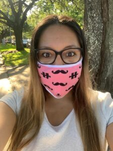 photo of Victoria in a cotton mask which is pink and has a black mustache and puzzle piece design